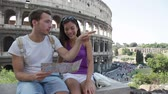 italiano : Tourists couple holding map by Colosseum sightseeing on travel vacation in Rome, Italy. Happy tourist couple, man and woman traveling on holidays in Europe happy. Interracial Asian Caucasian couple