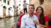 romantizm : Romantic travel couple in Venice on Gondola ride romance in boat talking happy together on travel vacation holidays. Young multiracial couple sailing in venetian canal in gondole. Italy, Europe Stok Video