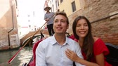 romantický : Tourists travel couple in Venice on Gondole boat ride enjoying romance in boat happy together on vacation holidays. Romantic young beautiful couple sailing in venetian canal in gondola. Asian woman.