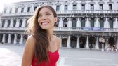 tatil : Venice woman tourist on San Marco Square, Italy. Smiling happy cheerful multiracial girl walking elegant in summer dress on San Marco Square, Venice, Italy. Caucasian Asian model looking at camera. Stok Video
