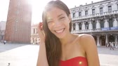 tatil : Woman smiling playful on San Marco Square, Italy. Tourist Smiling happy cheerful multiracial girl elegant in summer dress on San Marco Square, Venice, Italy. Caucasian Asian model looking at camera.