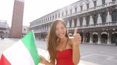 turístico : Woman waving Italian flag happy in Venice, Italy. Smiling cheerful multiracial girl having fun on San Marco Square, Venice, Italy. Caucasian Asian model giving thumbs up looking at camera.