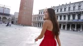 walk : Venice woman tourist walking on San Marco Square, Italy. Smiling happy cheerful multiracial girl elegant in summer dress on San Marco Square, Venice, Italy. Caucasian Asian model looking at camera.
