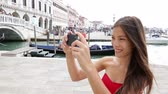 женщина : Smartphone woman taking picture in Venice, Italy. Woman smiling using mobile cell smart phone camera taking photo having fun by water in Venice. Beautiful multiracial Asian Caucasian young woman. Стоковые видеозаписи