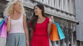italy : Shopping women happy holding shopping bags walking talking having fun laughing. Two beautiful young Asian woman, Caucasian woman girlfriends on travel vacation, Piazza San Marco Square, Venice, Italy. Stock Footage