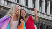 два человека : Girlfriends shopping laughing happy taking selfie photo with smartphone. Woman friends holding shopping bags while taking self-portrait picture with smart phone. Blonde girl and Asian woman, 20s