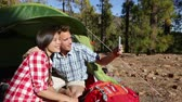 casal : Camping couple in tent taking smartphone selfie self portrait photo picture. Campers smiling happy outdoors in forest. Happy people having fun in outdoor activity. Asian woman, Caucasian man. Vídeos