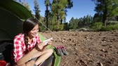 tabuleta digital : Tablet computer pc used by camping woman hiker in tent at campsite. Girl camper using tablet relaxing enjoying active outdoors lifestyle.