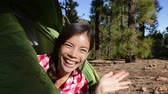 povo : Camping woman waving hello from tent smiling happy outdoors in forest. Happy girl saying hello and good morning opening tent. Smiling mixed race Asian Caucasian girl saying hi looking at camera. Vídeos