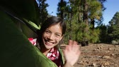 bom : Woman camping waving hello from tent smiling happy outdoors in forest. Happy girl saying hello and goodbye closing tent. Smiling mixed race Asian Caucasian girl saying hi looking at camera. Vídeos