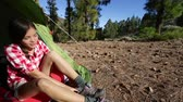 женщины : Camping woman tying hiking shoes walking from tent at campsite going on hike in forest. Beautiful young smiling happy mixed race Asian Caucasian female hiker model in outdoor activity.