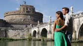 angel : Rome travel tourists by Castel SantAngelo. Happy romantic couple looking and pointing at the roman castle enjoying their romantic summer holidays travel in Italy, Europe. Man and woman embracing. Stock Footage