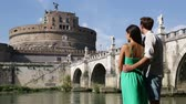 italy : Rome travel tourists by Castel SantAngelo. Happy romantic couple looking at the roman castle enjoying their romantic summer holidays travel in Italy, Europe. Man and woman embracing.