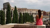 saying : Tourist girl in Italy looking at Colosseum, Rome, turning around waving hello looking at camera. Young woman enjoying travel vacation holidays in Roman Forum and view of Italian landmark, Coliseum..