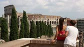 Řím : Colosseum, Rome - Couple tourists in Italy. Young couple enjoying romantic travel vacation holidays in Roman Forum enjoying view of the famous Italian landmark, Coliseum. Tourism in Rome, Italy.