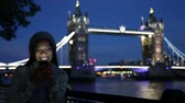 aplicativo : Smartphone woman on cell phone in London in front of Tower Bridge at night. Girl using app or texting sending sms text message with mobile phone by the River Thames, London, England, Great Britain.