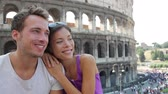 yolculuk : Couple of Tourist in Rome by Coliseum on travel smiling looking to side. Happy young tourists traveling in Italy. Beautiful asian woman and man in their 20s on holidays vacation in Italy, Europe