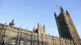 yönetme : Palace of Westminster, London, UK with British flag. Houses of Parliament in London, United Kingdom. The UK flag, Union Jack against clear blue sky.