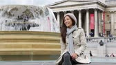 spojené království : London woman on Trafalgar Square smiling happy laughing having fun sitting and relaxing. Beautiful multiracial Asian Caucasian girl tourist on travel vacation in London, England, United Kingdom