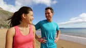 casal : Sporty runners resting talking before run on beach. Running athletes couple man and woman standing taking a break after jogging. Fit sport fitness couple living healthy active lifestyle. Vídeos