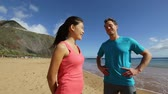 casal : Young couple talking starting running on beach. Athletes on break taking at rest smiling happy then starts jogging training workout. Exercising Asian woman and Caucasian fitness man.
