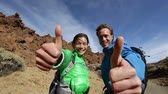 para cima : Thumbs up - hikers happy on Tenerife. Hiking couple excited looking at camera giving thumbs up hand sign gesture outdoors in nature on volcano Teide. Vídeos