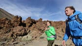 dráha : Hiking couple walking on hike on volcano Teide, Tenerife. Hikers trekking on trail path living active hiker outdoor lifestyle on Canary Islands, Spain Dostupné videozáznamy