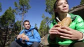 dişliler : Eating hiking people taking break enjoying food outdoors in mountain forest during hike. Woman and man hikers on Tenerife, Canary Islands, Spain. Stok Video