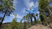 skály : Success winner - man hiker cheering happy stretching arms up after reaching goal and summit climbing rock. Excited cheerful male hiking in mountain forest on Teide, Tenerife, Canary Islands, Spain.