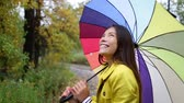 arco íris : Fall  Autumn concept - woman excited under rain with umbrella. Beautiful young female wearing raincoat surprised and excited in the rain. Mixed race Asian Caucasian girl in her 20s walking in forest.