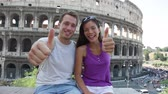 saying : Travel couple waving hello hands by Colosseum, Rome, Italy. Smiling young romantic couple traveling in Europe looking at camera smiling in front of Coliseum. Caucasian man and Asian woman.