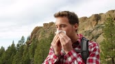 doku : Man blowing nose outside. Male hiker with allergy and running nose outdoors. Stok Video