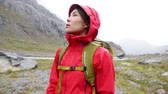 chuva : Hiker turning around looking for hike trail path in rain. Hiking woman in raincoat hardshell jacket wearing backpack in rainy bad weather. Girl walking in Swiss Alps, Switzerland.
