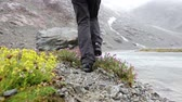czerwony : Hiking shoes on woman hiker walking in nature trekking by river outdoors in rain. Female and hiking boots outdoors in Swiss alps, Switzerland.