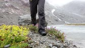 para cima : Hiking - woman hiker walking in nature. Closeup of hiking shoes boots trekking by river outdoors in rain. Female and trekking boots outdoors in Swiss alps, Switzerland.