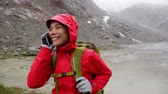 tecnologia : Smart phone woman calling talking on smartphone. Girl on mobile cell phone outside in nature in rain hiking in mountain wearing raincoat. Asian woman smiling laughing in Swiss Alps, Switzerland. Vídeos