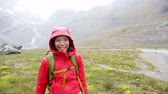 chuva : Thumbs up hiking woman happy looking at camera smiling happy and positive on hike in rain in mountain. Multicultural Asian Caucasian female trekking showing success hand sign in Swiss Alps Switzerland Stock Footage