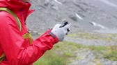 fabric : Smartphone woman texting sms using app on smart phone with touchscreen gloves. Closeup of mobile phone and female hands outside in nature in rain. Girl with glove of conductive fabric for touch screen.