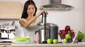 perda de peso : Apple juice - woman juicing apples and vegetables and drinking it fresh at home in kitchen giving thumbs up. Juice machine and healthy eating happy woman making green vegetable and fruit juice.