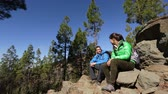 female : Hikers taking break sitting down talking on hike together on hike outdoors in mountain forest during hike. Hiking woman and man hikers on Tenerife, Canary Islands, Spain.