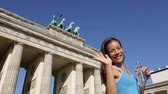 alemão : Woman waving hand saying hello running in Berlin, Germany by Brandenburg Gate. Athlete jogging living healthy lifestyle. Female runner jogging. Urban fitness girl working out outdoors.