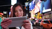turístico : Tablet computer - woman using app in New York City, Time Square, Manhattan. Girl tourist or New Yorker on small tablet pc at night. Lifestyle video with beautiful multiracial woman in her 20s.