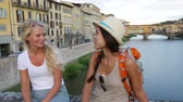 dva lidé : Friends on travel. Happy women girl friends traveling in Florence talking together. Cheerful girlfriends smiling happy in conversation outdoor by Ponte Vecchio during vacation holidays in Florence, Tuscany, Italy.