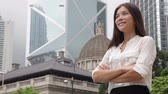 propriedade : Asian business woman confident outdoor in Hong Kong standing proud in suit cross-armed in business district. Young mixed race female Chinese Asian  Caucasian female professional in central Hong Kong. Stock Footage