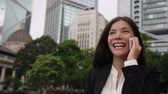 iş : Business people - woman on smart phone, Hong Kong. Asian business woman office worker talking on smartphone smiling happy. Young multiracial Chinese Asian  Caucasian female professional in Hong Kong. Stok Video