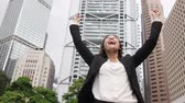 iş : Business success with successful woman in Hong Kong celebrating business achievements with arms spread out winning. Young mixed race Chinese Asian  Caucasian female professional in Hong Kong central. Stok Video