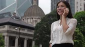 call : Businesswoman talking on phone outdoor, Hong Kong. Asian business woman people office worker talking on smartphone smiling happy. Young multiracial Chinese Asian  Caucasian female professional.