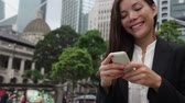 propriedade : Asian businesswoman talking on smartphone in Hong Kong. Asian business woman people office worker talking on smartphone smiling happy. Young multiracial Chinese Asian  Caucasian female professional.
