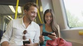 taşıma : Smart phone people sharing and watching funny video laughing traveling in train on commute. Passengers using smartphone commuting in public transportation. Young multiracial Asian woman  Caucasian Man Stok Video