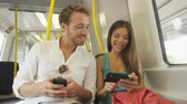 metro : People on smart phone sharing and watching funny video laughing traveling in train on commute. Passengers using smartphone commuting in public transportation. Multiracial Asian woman  Caucasian Man
